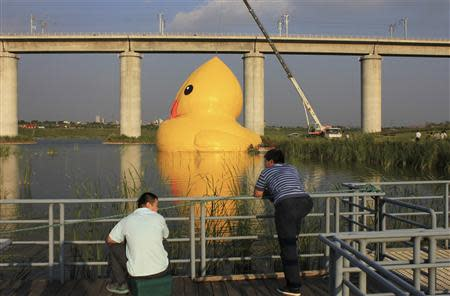 People look on as an inflated Rubber Duck by Dutch conceptual artist Florentijn Hofman is set up next to a high-speed railway viaduct bridge on a lake at the 9th China International Garden Expo in Beijing, September 5, 2013. REUTERS/Stringer