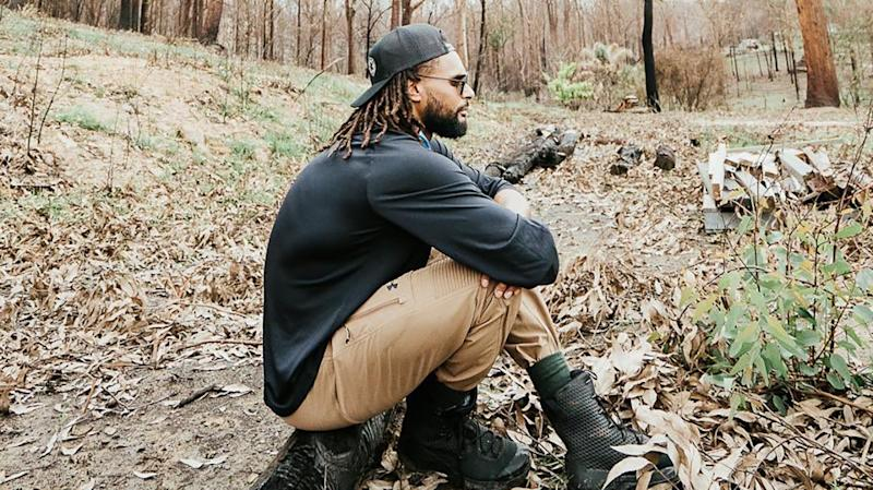 Australian NBA star Patty Mills is pictured surveying the scene of a bushfire during a visit in February.
