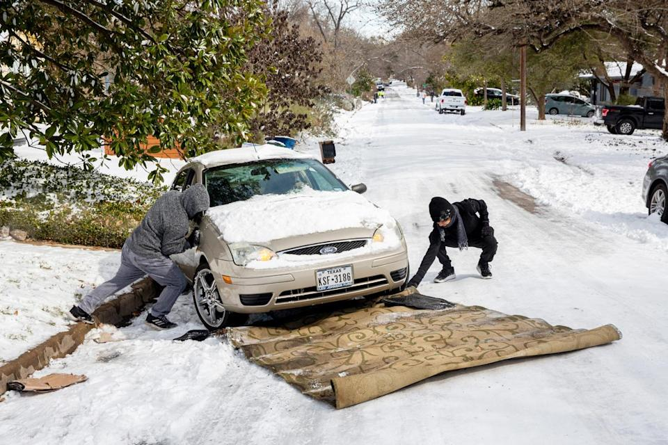 <p>Ivan Gonzales (left) and his brother-in-law Gabriel Martinez assist a motorist by using a carpet to help them up a hill in Austin, Texas. </p>