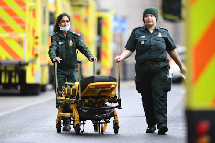 Paramedics wheel a stretcher at the Royal London hospital in London on January 12, 2021 as surging cases of the novel coronavirus are placing health services under increasing pressure. (Photo by DANIEL LEAL-OLIVAS / AFP) (Photo by DANIEL LEAL-OLIVAS/AFP via Getty Images)
