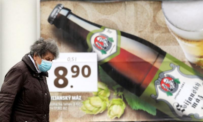 A woman walks past a beer advertisement billboard in Prague