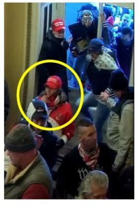 Surveillance video shows the woman in the American flag jacket enter the U.S. Capitol through a broken window near the Senate Wing Door. The woman remained in the Senate Wing Door lobby area for a period of time where she took pictures and engaged with U.S. Capitol Police officers.