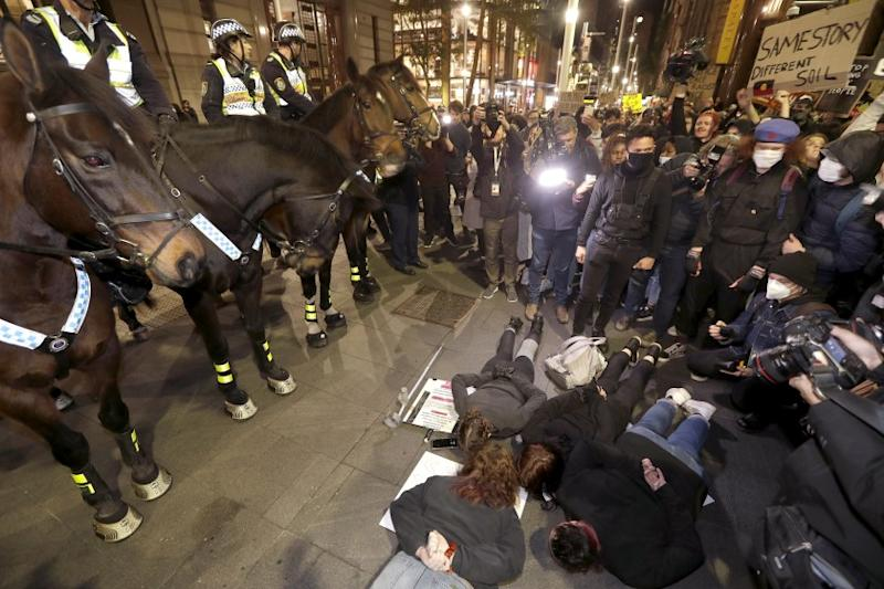 Protestors lay on the ground in front of police on horseback as they gather in Sydney, Tuesday, June 2, 2020, to support the cause of U.S. protests over the death of George Floyd and urged their own governments to address racism and police violence. Floyd died last week after he was pinned to the pavement by a white police officer who put his knee on the handcuffed black man's neck until he stopped breathing. (AP Photo/Rick Rycroft)