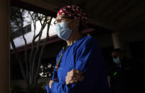 Nurse Teri Wheat walks outside a hospital in Fort Worth, Texas, Thursday, Nov. 19, 2020. As Wheat recently made her rounds at a Texas maternity ward, she began to realize she was having a hard time understanding the new mothers who were wearing masks due to the coronavirus pandemic. Hearing specialists across the U.S. say they have seen an uptick in visits from people like Wheat, who only realized how much they relied on lip reading and facial expressions when people started wearing masks that cover the nose and mouth. (AP Photo/LM Otero)