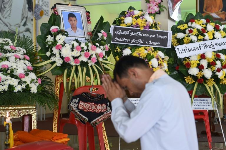 A mourner prays in front of a portrait of 13-year-old Muay Thai boxer Anucha Tasako next to his coffin during a funeral at a Buddhist temple in Samut Prakan province on November 14, 2018. Thais have reacted with shock and anger after Tasako died during a charity bout, reviving calls for a ban on fights between children in the brutal Muay Thai martial art