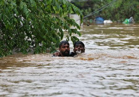 FILE PHOTO: A man rescues a drowning man from a flooded area after the opening of Idamalayr, Cheruthoni and Mullaperiyar dam shutters following heavy rains, on the outskirts of Kochi