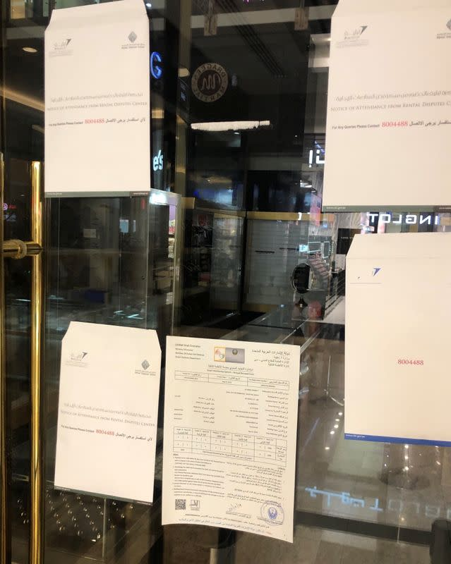 Rental dispute notices hang on a shop window in Dubai