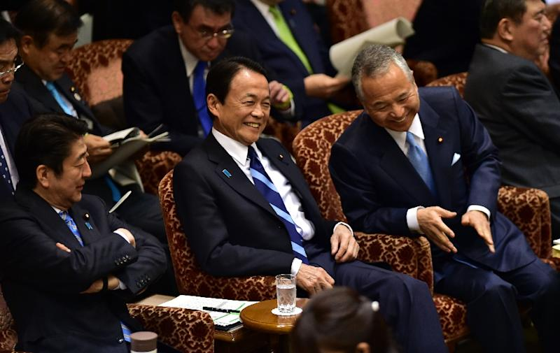 Japan's Economic Revitalization Minister Akira Amari (R) shares a joke with Prime Minister Shinzo Abe (L) and Finance Minister Taro Aso before the Upper House's audit committee session, at the National Diet in Tokyo, on January 21, 2016 (AFP Photo/Yoshikazu Tsuno)