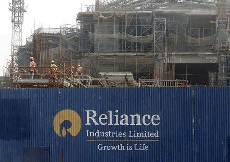 FILE PHOTO: Labourers work behind an advertisement of Reliance Industries Limited at a construction site in Mumbai