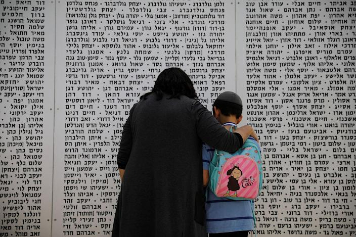 <p>A woman and a boy look at a memorial wall, engraved with names of fallen soldiers from the armoured corps, during a Memorial Day ceremony in Latrun, Israel May 1, 2017 (Amir Cohen/Reuters) </p>