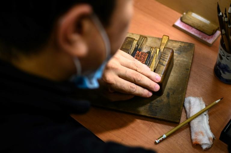 Traditional ink stamp-maker Takahiro Makino working on a hanko in Tokyo