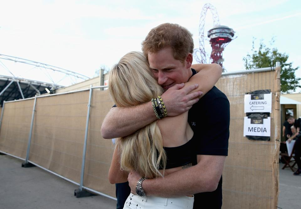 LONDON, ENGLAND - SEPTEMBER 14:  Prince Harry hugs Ellie Goulding backstage at the Invictus Games Closing Ceremony during the Invictus Games at Queen Elizabeth park on September 14, 2014 in London, England. The International sports event for 'wounded warriors', presented by Jaguar Land Rover was an idea developed by Prince Harry after he visited the Warrior Games in Colorado USA. The four day event has brought together thirteen teams from around the world to compete in nine events such as wheelchair basketball and sitting volleyball.  (Photo by Chris Jackson/Getty Images)