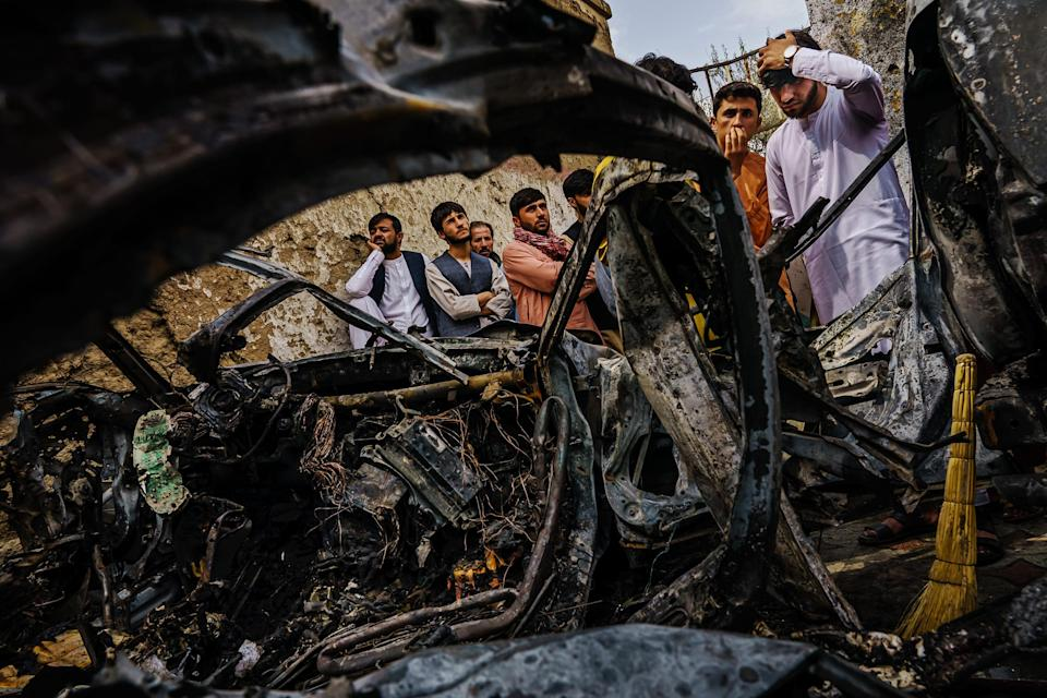 Relatives and neighbors of the Ahmadi family gathered on Aug. 30, 2021, around the incinerated husk of a vehicle targeted a day earlier by the American drone strike.
