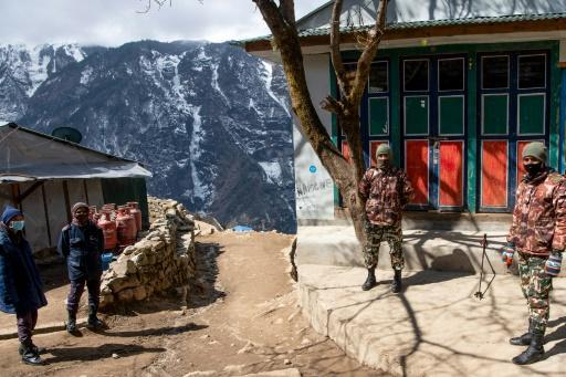 Security personnel stand guard during a nationwide lockdown in Namche Bazar in the Everest region -- thousands of tourists and trekkers are stranded in far-flung areas of Nepal