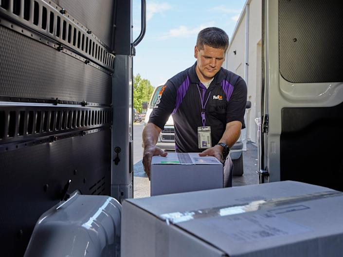 A FedEx delivery person takes a box out of a truck.