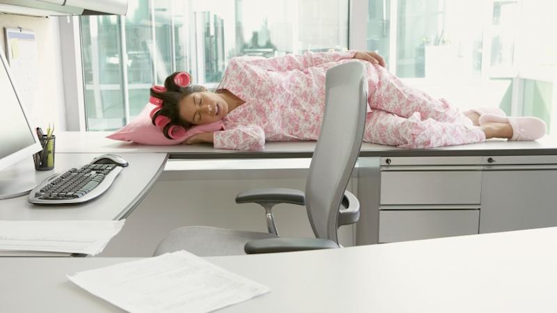 A woman in pyjamas and hair curlers sleeping on her desk at work.
