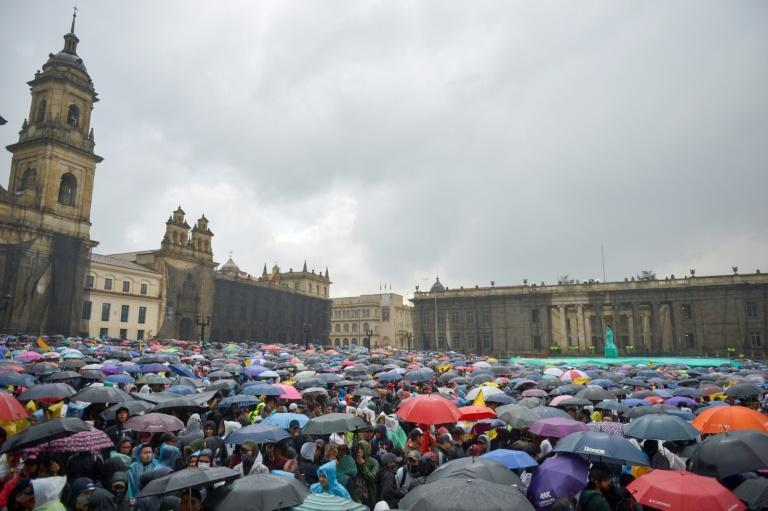 People demonstrate under pouring rain at Bolivar square in Bogota during a general strike to protest government policies