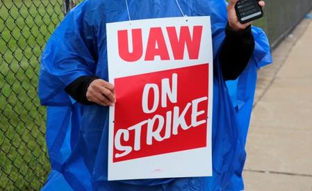 Member of United Auto Workers, Aramark workers, carries a strike sign outside the General Motors Detroit-Hamtramck assembly plant in Detroit