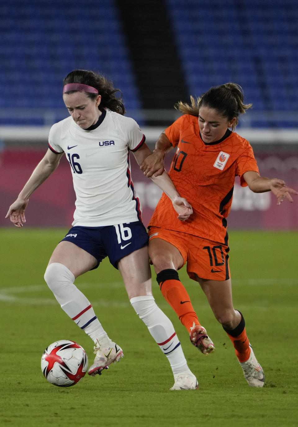 United States' Rose Lavelle, left, and Netherlands' Danielle van de Donk battle for the ball during a women's quarterfinal soccer match at the 2020 Summer Olympics, Friday, July 30, 2021, in Yokohama, Japan. (AP Photo/Kiichiro Sato)