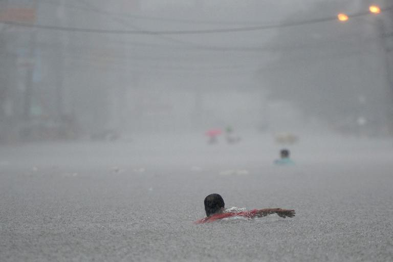 A resident swims along a flooded street during heavy rains brought on by Tropical Storm Fung-Wong in Manila on September 19, 2014