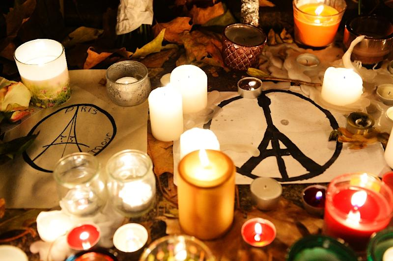Candles and messages are seen left at a makeshift memorial next to the Bataclan concert hall in Paris on November 16, 2015 (AFP Photo/Bertrand Guay)