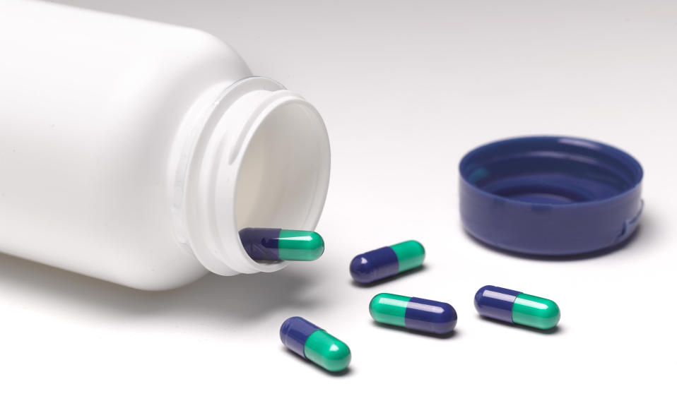 Capsules left lying on table, with open pill bottle