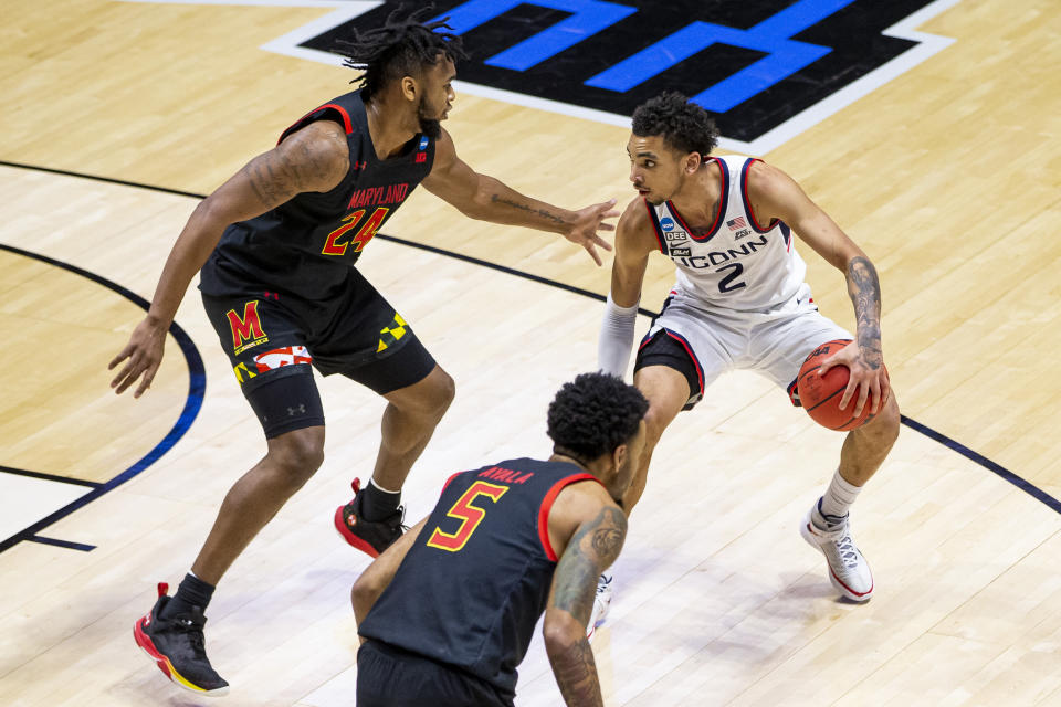 Connecticut's James Bouknight (2) gets pressure from Maryland's Donta Scott (24) and Eric Ayala (5) during the second half of a first-round game in the NCAA men's college basketball tournament Saturday, March 20, 2021, at Mackey Arena in West Lafayette, Ind. Maryland won 63-54. (AP Photo/Robert Franklin)