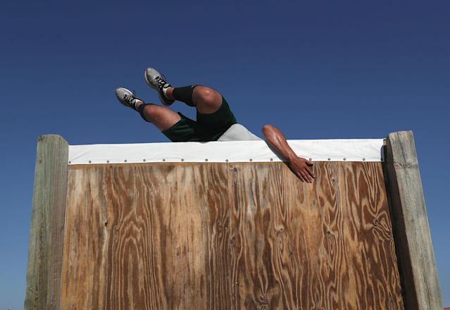 <p>A U.S. Border Patrol trainee climbs over an obstacle course wall at the U.S. Border Patrol Academy on August 3, 2017 in Artesia, N.M. (Photo: John Moore/Getty Images) </p>