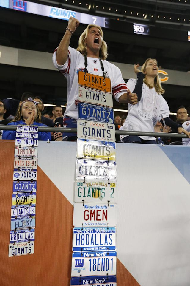 New York Giants fan Joe Ruback, center, cheers with his daughter Isabella, left, and wife, Sarah, during the first half of an NFL football game between the Giants and the Chicago Bears, Thursday, Oct. 10, 2013, in Chicago. (AP Photo/Charles Rex Arbogast)
