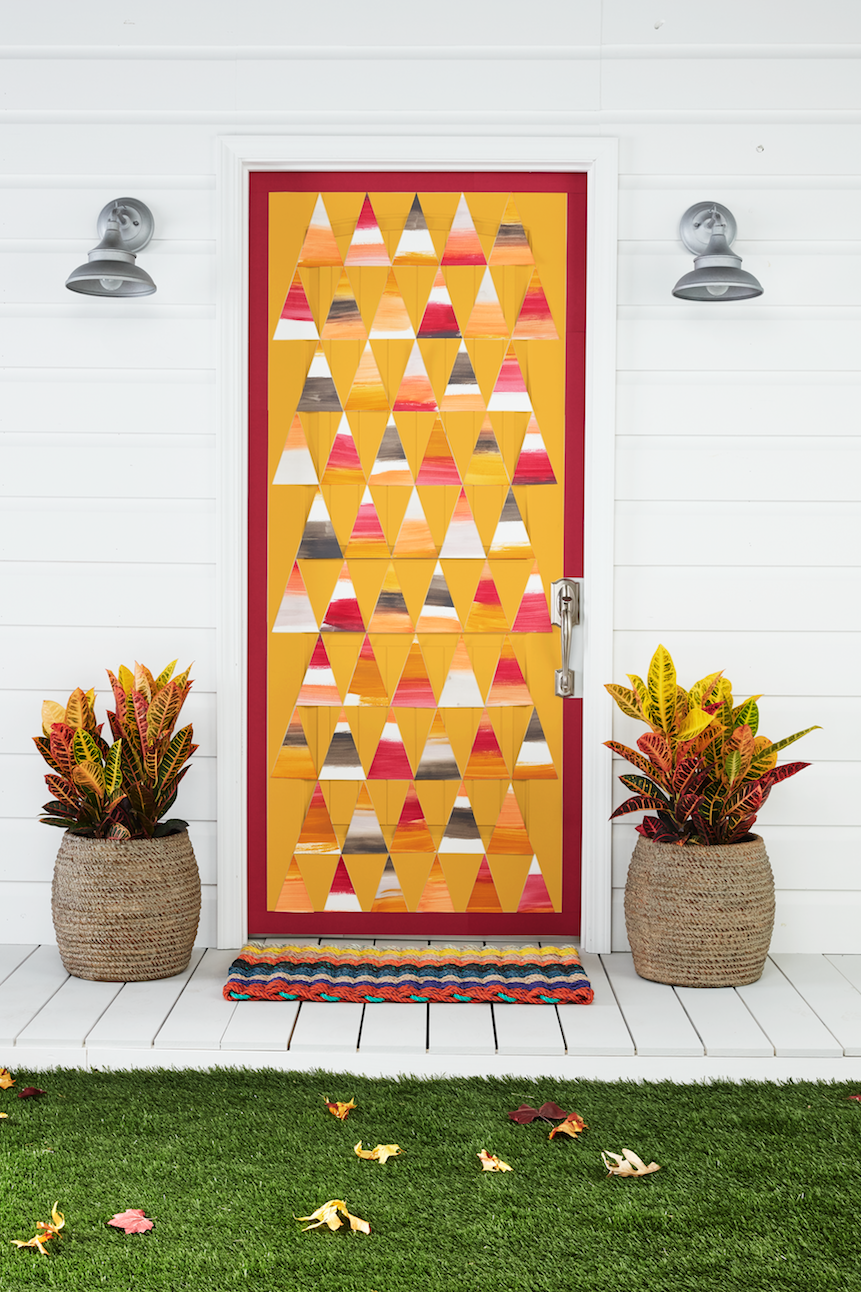 "<p>Can't figure out what to put on your door? Get inspired by your favorite <a href=""https://www.countryliving.com/food-drinks/g615/halloween-sweets-1008/"" rel=""nofollow noopener"" target=""_blank"" data-ylk=""slk:Halloween sweets"" class=""link rapid-noclick-resp"">Halloween sweets</a>—like candy corn!</p><p><strong>Make the Candy Corn Door: </strong>Create a candy corn-inspired ""quilt."" Paint wide stripes, using acrylic paint (we used orange, mustard, cranberry, and gray), on thick artist's paper. Once dry, cut into equal-size triangles. Cut a 2-inch paper trim in a corresponding color. Attach to door using double- sided tape. Add whitewashed woven planters and ""Lobster Rope"" doormat. </p><p><a class=""link rapid-noclick-resp"" href=""https://www.amazon.com/Art-Supply-Premium-Spiral-100-Sheets/dp/B00PG6VN1S/?tag=syn-yahoo-20&ascsubtag=%5Bartid%7C10050.g.22350299%5Bsrc%7Cyahoo-us"" rel=""nofollow noopener"" target=""_blank"" data-ylk=""slk:SHOP ARTIST'S PAPER"">SHOP ARTIST'S PAPER</a></p>"