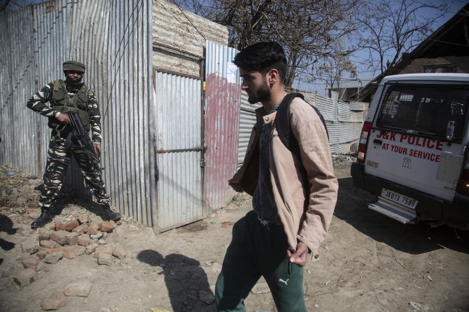 An Indian paramilitary soldier stands guard as a Kashmiri displays the insides of his clothing as he passes near the site of a shootout in Srinagar, Indian controlled Kashmir, Friday, Feb. 19, 2021. Anti-India rebels in Indian-controlled Kashmir killed two police officers in an attack Friday in the disputed region's main city, officials said. Elsewhere in the Himalayan region, three suspected rebels and a policeman were killed in two gunbattles. (AP Photo/Mukhtar Khan)