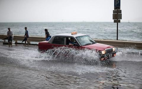 A taxi drives on a flooded street as typhoon Hato passes Hong Kong, - Credit: EPA