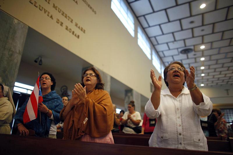 People attend a Mass in honor of Puerto Rico's Archbishop Roberto Gonzalez Nieves at a church in San Juan, Puerto Rico, Wednesday, May 8, 2013. Roman Catholics in Puerto Rico rallied Wednesday around the archbishop who is apparently under pressure from the Vatican to resign for allegedly covering up for sexually abusive priests and other misdeeds. Archbishop Roberto Gonzalez Nieves has not confirmed that he is being asked to step down as leader of the Catholic Church in the U.S. island territory. However, he has asked parishioners to pray for him. (AP Photo/Ricardo Arduengo)