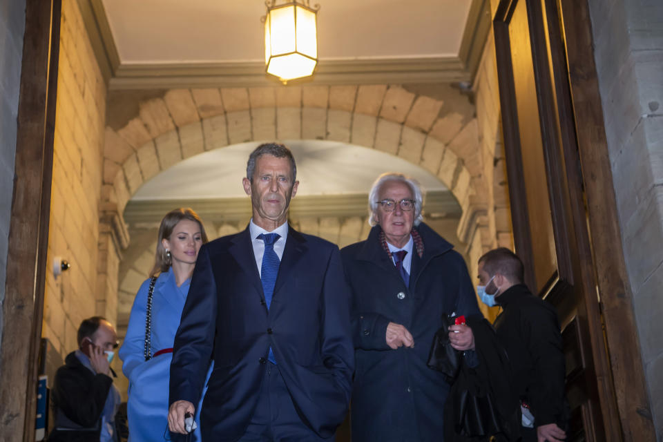 Lawyers Camille Haab, left, and Marc Bonnant, right, lawyer for Israeli businessman and diamond magnate Beny Steinmetz, at center, leaving the courthouse in Geneva, Switzerland, Friday Jan. 22, 2021. Mining tycoon Steinmetz has been sentenced to five years in jail and fined dollars 56.5m after being found guilty of bribery, Friday. Steinmetz said he would appeal against the judgment. (Martial Trezzini/Keystone via AP)