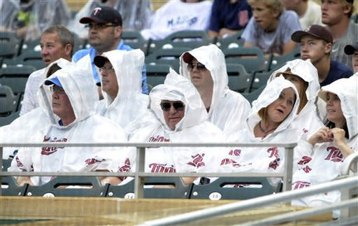 Minnesota Twins fans brave rain during a baseball game against the Milwaukee Brewers, Sunday, June 17, 2012, in Minneapolis. The game continued until heavier rain forced a delay after 11 innings. (AP Photo/Jim Mone)