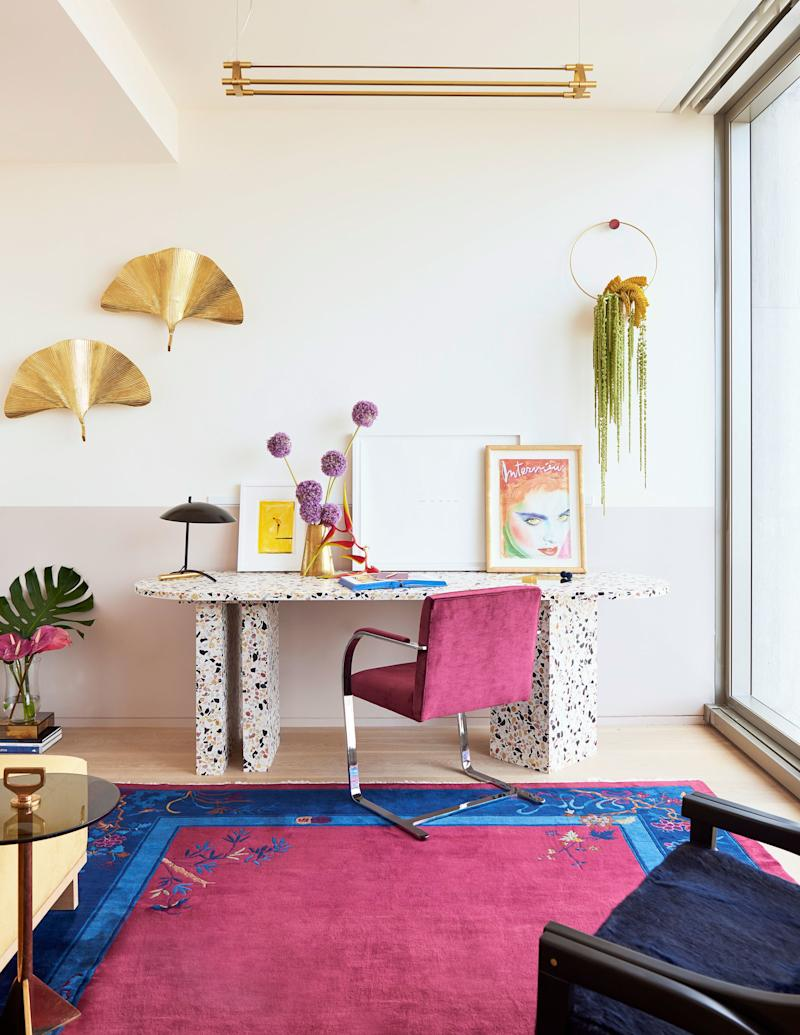 """One of the home's most eye-catching pieces is this custom desk, made of poured terrazzo and inset with bits of mirror and inspired by Miami in the 1980s. """"We had seven or eight meetings about the desk,"""" says Angelo. """"It was a true collaboration with us and Armann."""" The fuchsia chair is a Mies van der Rohe Brno model, paired with a vintage Art Deco rug in matching colors."""