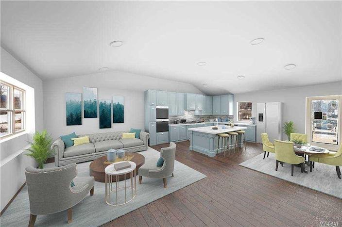 A living room and kitchen area in a new, 3D-printed room with white walls and blue cabinets