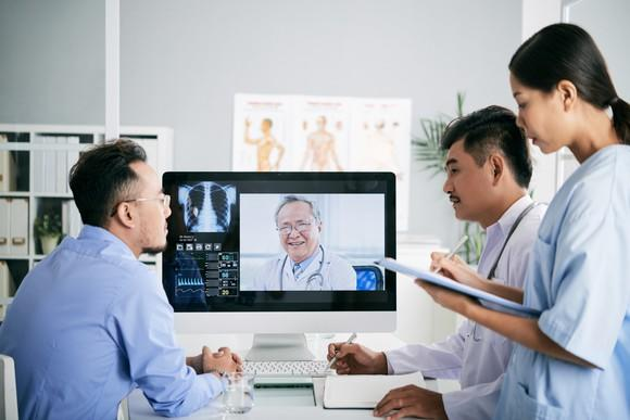 Doctors having a teleconference on screen with another doctor.