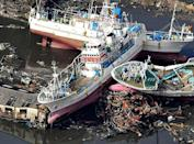 Vessels get stranded in Kesennuma, Miyagi prefecture, northern Japan, Saturday, March 12, 2011, after being washed away by an earthquake-triggered tsunami. The powerful tsunami created by one of the strongest earthquakes ever recorded swept away Japan's east coast Friday. (AP Photo/The Yomiuri Shimbum, Kenji Shimizu)