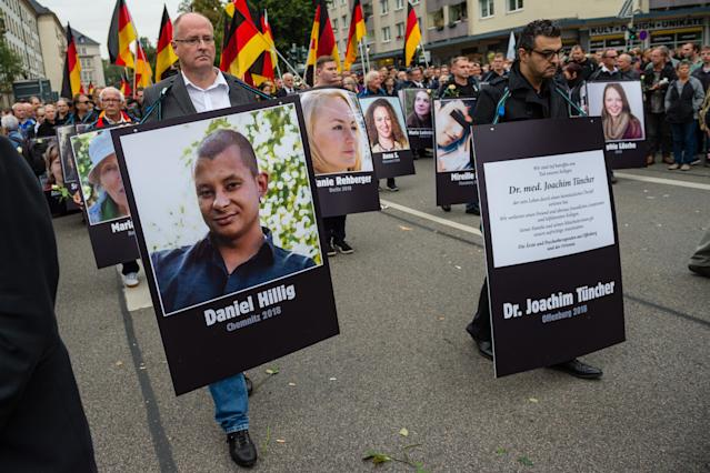 <p>People take part in a march of silence organized by the right-wing Alternative for Germany (AfD) political party and carry German flags and portraits of supposed victims of refugee violence on Sept. 1, 2018 in Chemnitz, Germany. Two refugees, a Syrian and an Iraqi, are accused of having stabbed Chemnitz local Daniel Hillig following an altercation in the early hours of August 26. The death has sparked angry protests by locals as well as right-wing groups that have led to clashes with police and counter-protesters. (Photo: Jens Schlueter/Getty Images) </p>