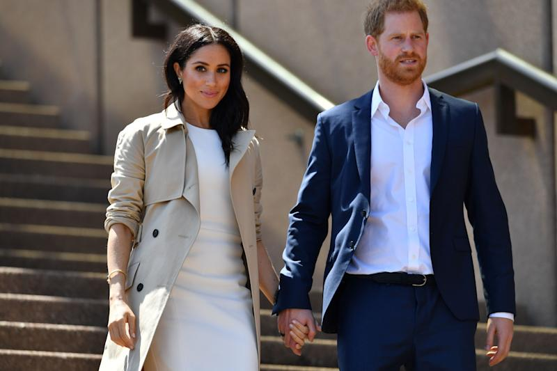 Britain's Prince Harry and his wife Meghan walk down the stairs of Sydneys iconic Opera House to meet people in Sydney on October 16, 2018. - Prince Harry and Meghan have made their first appearances since announcing they are expecting a baby, kicking off a high-profile Pacific trip with a photo in front of Sydney's dazzling Opera House and posing with koalas. Meghan wore a pair of butterfly earrings and a gold bracelet which belonged to Prince Harry's mother, the late Princess Diana. (Photo by SAEED KHAN / AFP) (Photo credit should read SAEED KHAN/AFP via Getty Images)