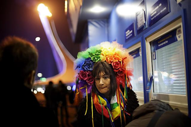 Vladimir Luxuria, a former Communist lawmaker in the Italian parliament and prominent crusader for transgender rights, waits to receive her ticket at a box office for a women's ice hockey match as the Olympic flame burns in the background at the 2014 Winter Olympics, Monday, Feb. 17, 2014, in Sochi, Russia. Luxuria was soon after detained by police upon entering the Shayba Arena to attend the women's ice hockey match