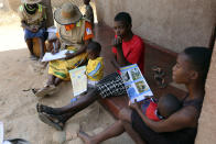 Community health worker, Rosemary Rambire, left, takes notes during a COVID-19 awareness campaign in Chitungwiza, on the outskirts of Harare, Wednesday, Sept. 23, 2020. As the Zimbabwe's coronavirus infections decline, strict lockdowns designed to curb the disease are being replaced by a return to relatively normal life. The threat has eased so much that many people see no need to be cautious, which has invited complacency. That worries some health experts. Rosemary Rambire says the improving figures and the start of the searing heat of the Southern Hemisphere's summer could undermine efforts to beat back the virus even further. (AP Photo/Tsvangirayi Mukwazhi)