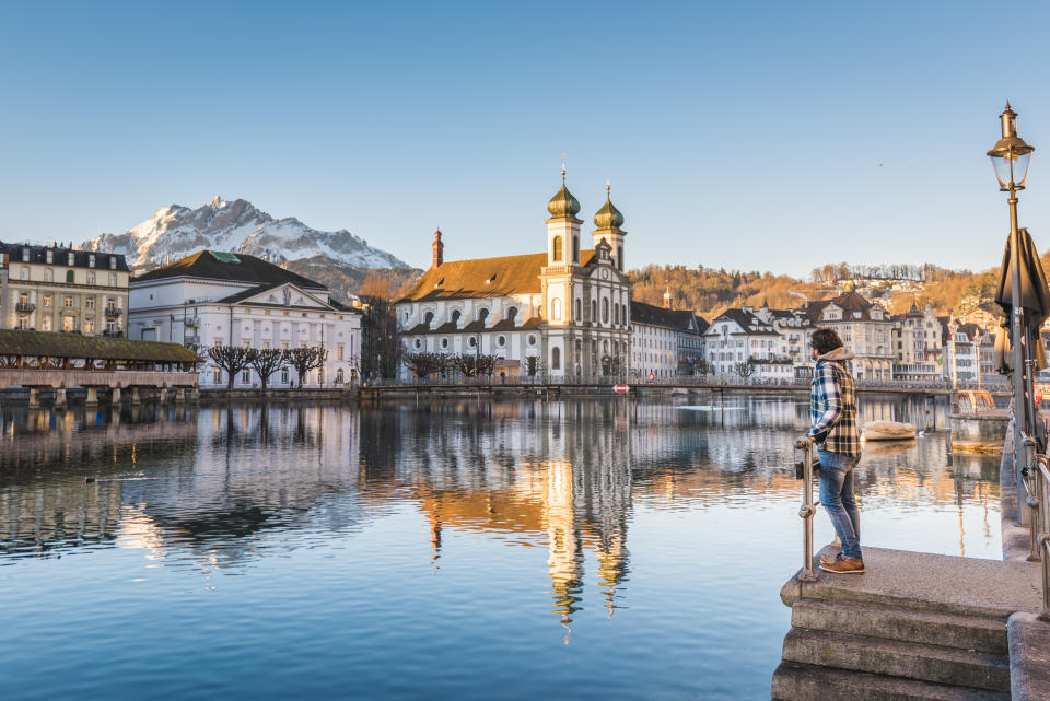 One man looking at the Jesuit Church and Mount Pilatus from the banks of Reuss river in Lucerne, Switzerland