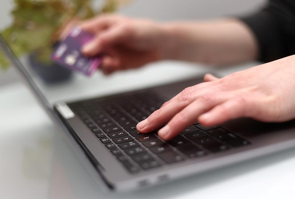 Woman holds credit card while using laptop