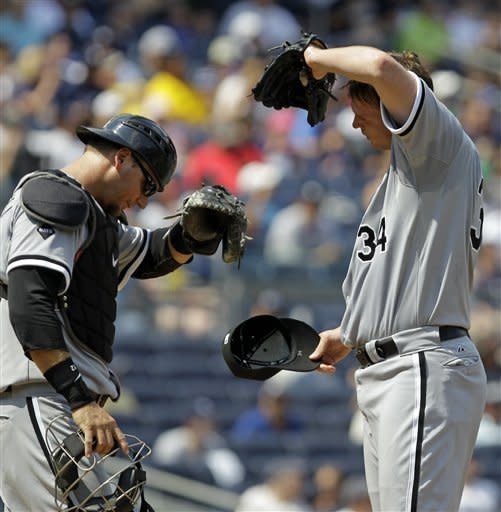 Chicago White Sox catcher A.J. Pierzynski, left, and Chicago White Sox starting pitcher Gavin Floyd wipe their brows because of the high heat and humidity at their baseball game at Yankee Stadium in New York, Sunday, July 1, 2012. (AP Photo/Kathy Willens)