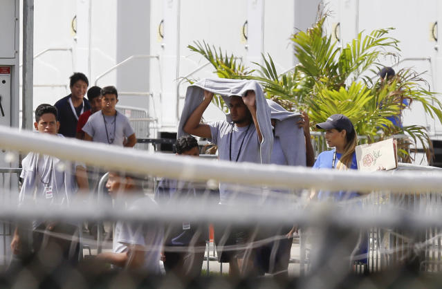 <p>Migrant children walk outside at the Homestead Temporary Shelter for Unaccompanied Children a former Job Corps site that now houses them, on Friday, June 22, 2018, in Homestead, Fla. U.S. officials provided a glimpse into the South Florida facility housing more than 1,000 teen-age migrants, seeking to dispel any suggestions that children are being mistreated. The tour included dorm-style buildings where children sleep up to 12 per room in steel-framed bunk beds, and warehouse-sized, air-conditioned white tents where minors attend classes and watch movies. (Photo: Brynn Anderson/AP) </p>