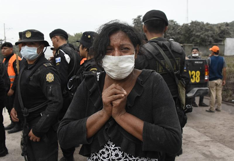A woman cries for her missing relatives during the search for vicitms in San Miguel Los Lotes, a village in Escuintla Department, about 35 km southwest of Guatemala City, on June 4, 2018, a day after the eruption of the Fuego Volcano (AFP Photo/Johan ORDONEZ)