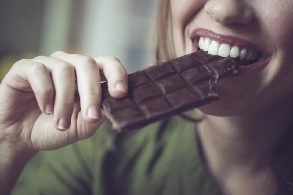 close up shot of a woman biting into a block of chocolate