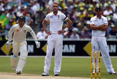 Australia's captain Clarke runs between wickets as England's captain Cook and bowler Broad look on during the second day's play in the second Ashes cricket test at the Adelaide Oval